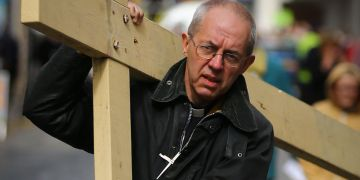 The Archbishop of Canterbury Justin Welby carries a cross through Dover, Kent, during the Procession of Witness ahead of delivering a sermon in the market square.
